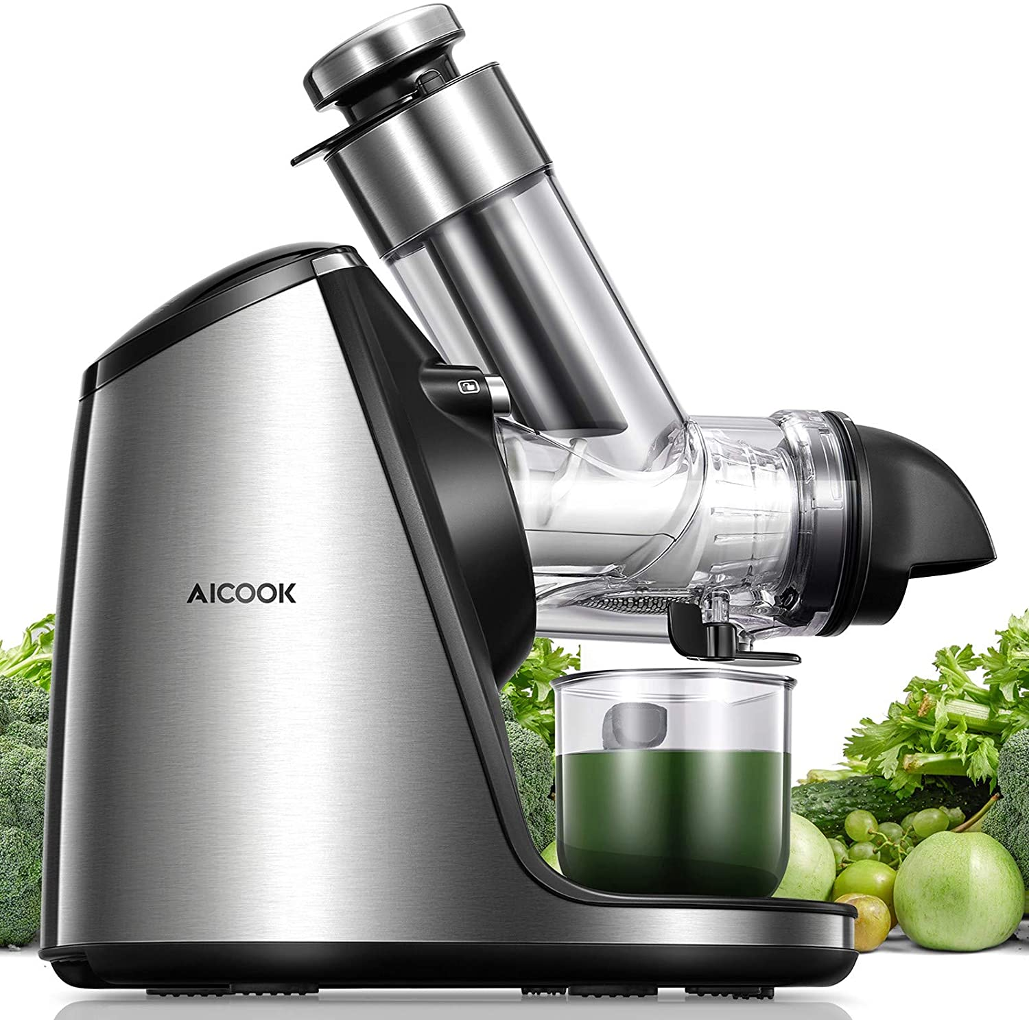 A silver slow juicer surrounded by green fruits depositing green juice into a clear glass cup
